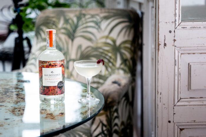 Bax Botanics bottle on table with Sea Buckthorn cocktail.